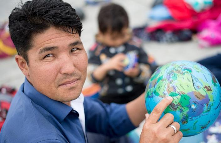 A refugee points at his home country, Afghanistan, as he rests at the Hungarian-Austrian border near the Austrian village of Nickelsdorf on September 5, 2015 (AFP Photo/Joe Klamar)