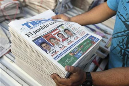 A vendor arranges newspapers covering the preliminary tally of presidential candidates on front page, in Tegucigalpa