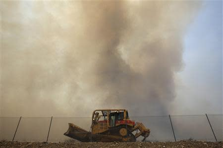 Smoke rises behind a firefighting bulldozer as a wildfire driven by fierce Santa Ana winds blows in Rancho Cucamonga, California, April 30, 2014. REUTERS/David McNew