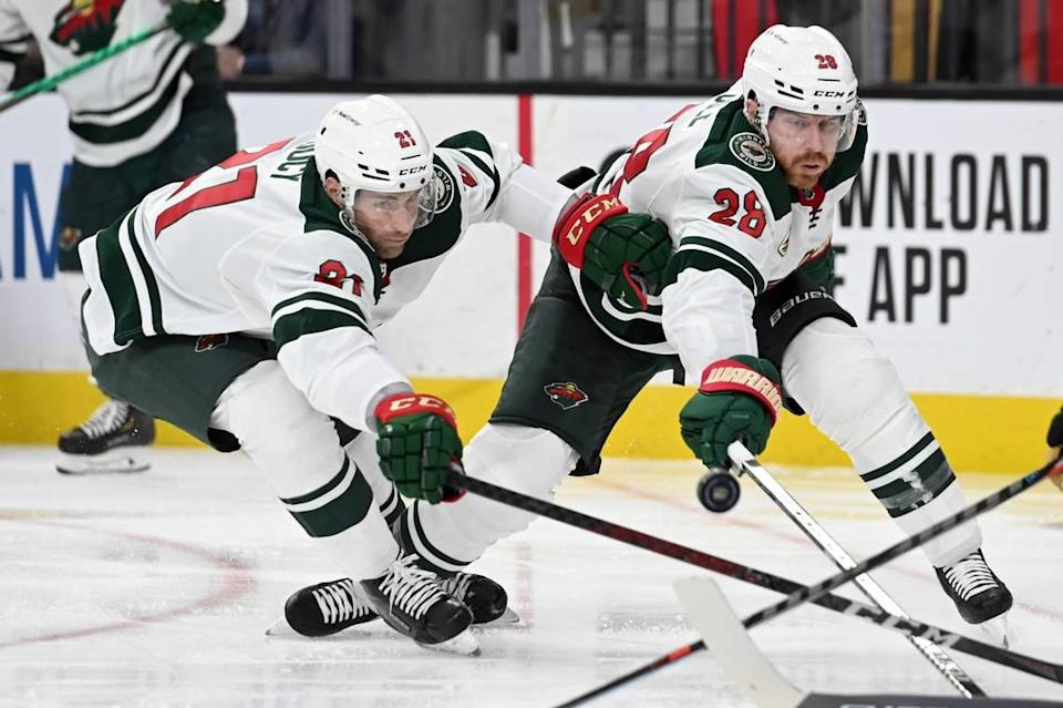 Minnesota Wild defenseman Carson Soucy (21) and defenseman Ian Cole (28) reach for the puck during the second period of Game 2 of the team's first-round NHL hockey playoff series against the Vegas Golden Knights on Tuesday, May 18, 2021, in Las Vegas. (AP Photo/David Becker)