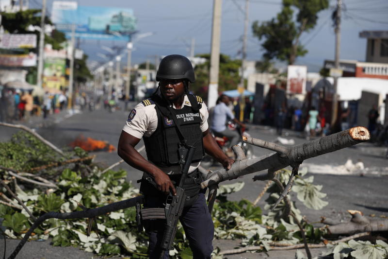 A policeman dismantles a barricade set up by protesters demanding the resignation of Haitian President Jovenel Moise, in Port-au-Prince, Haiti, Monday, Oct. 7, 2019. The country enters its fourth week of protests that have paralyzed the economy. (AP Photo/Rebecca Blackwell)