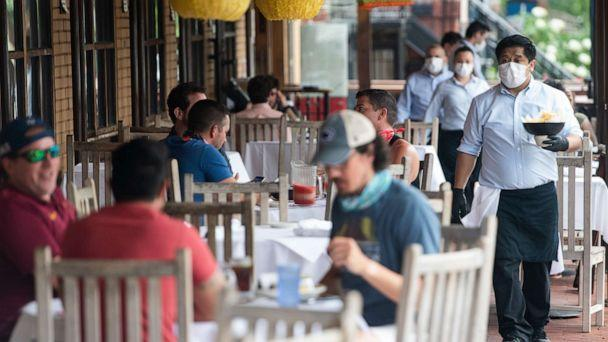 PHOTO: A waiter wearing a mask and gloves delivers food to a table to customers seated at an outdoor patio at a Mexican restaurant in Washington, May 29, 2020. (Saul Loeb/AFP via Getty Images)
