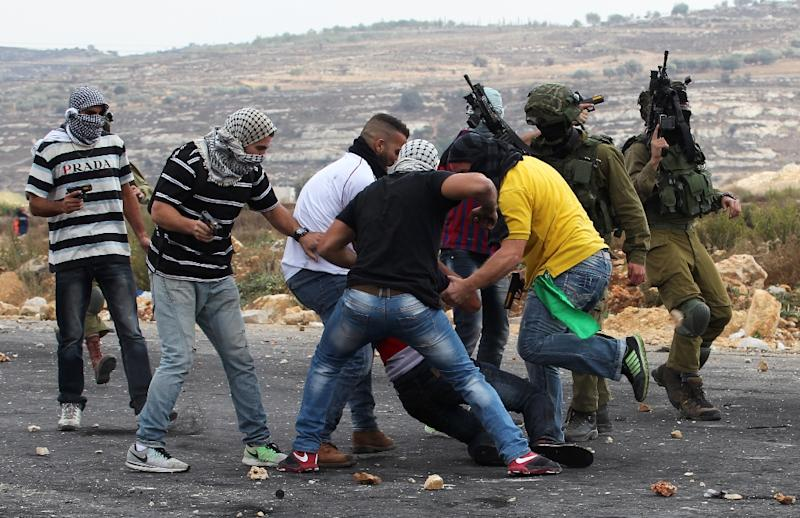 Israeli soldiers and infiltrated members of the Israeli security forces detain a Palestinian stone thrower during clashes in Beit El, on the outskirts of the West Bank city of Ramallah, on October 7, 2015 (AFP Photo/Abbas Momani)
