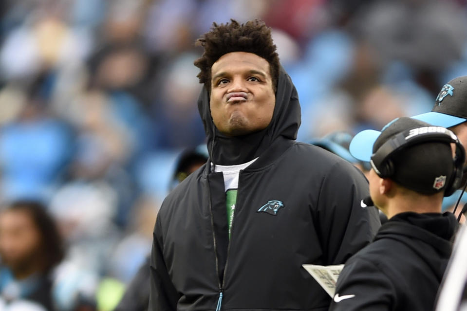 Cam Newton watches the action from the sideline during a Panthers game.