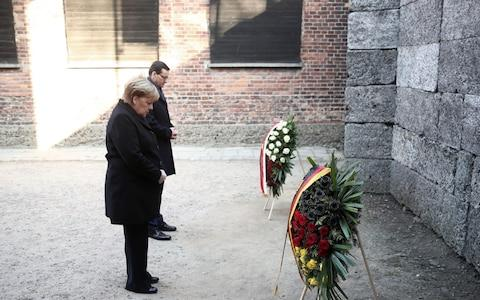 <span>Mrs Merkel laid a wreath at the Death Wall where thousands of prisoners were executed</span> <span>Credit: LUKASZ GAGULSKI/EPA-EFE/REX </span>