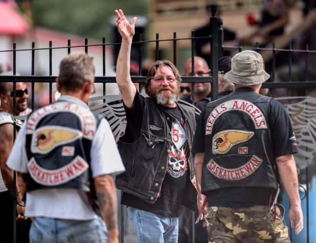 A member of the Hells Angels waves towards photographers as he enters the Hells Angels Nomads compound during the group's Canada Run event in Carlsbad Springs, Ont., near Ottawa, on Saturday, July 23, 2016.