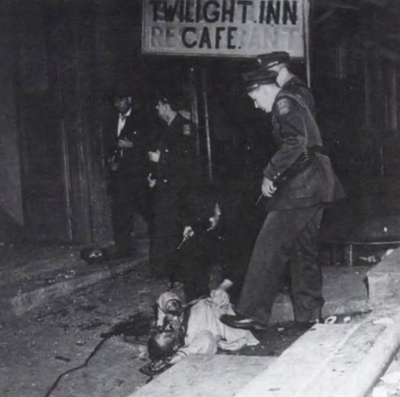 John Blackwell lies in the street after being beaten and dragged down the steps of the Loge Hall during the Tennessee Highway Patrol's early morning raid of Columbia's Black business district, the Bottom, on Feb. 26, 1946. Policeman Frank T. Collins and Constable Homer Copeland are seen passing in the background.