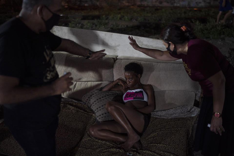 "Members of the God's Love Evangelical Church and Rehab Center pray for a woman in an area known as ""cracolandia"" (crackland) amid the COVID-19 pandemic in Rio de Janeiro, Brazil, Friday, March 19, 2021. (AP Photo/Felipe Dana)"