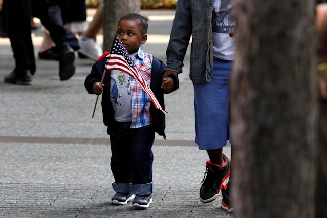 <p>A young boy carries an American flag as people gather at the National 911 Memorial and Museum during ceremonies marking the 16th anniversary of the September 11, 2001 attacks in New York, Sept. 11, 2017. (Photo: Brendan McDermid/Reuters) </p>