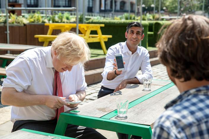 British Prime Minister Boris Johnson and Chancellor Rishi Sunak use their phones during a visit to a restaurant in London, June 26, 2020. The U.K. government had to scrap its initial effort to develop a contact-tracing app. (Photo: WPA Pool via Getty Images)