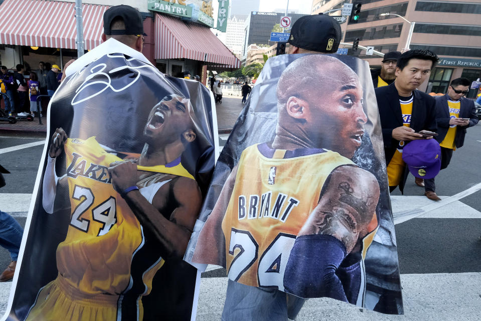 Fans carry posters of Kobe Bryant near the Staples Center before a public memorial for former Los Angeles Lakers star Kobe Bryant and his daughter, Gianna, in Los Angeles, Monday, Feb. 24, 2020. (AP Photo/Ringo H.W. Chiu)