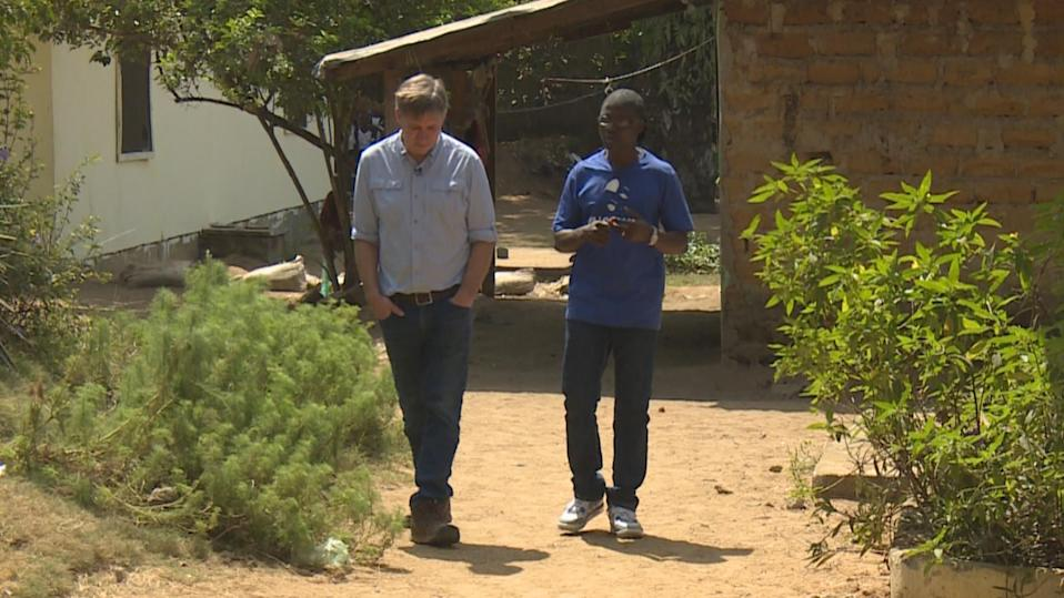 Steve Hartman discusses this unlikely story with Joel in Liberia. (Photo: CBS Evening News)