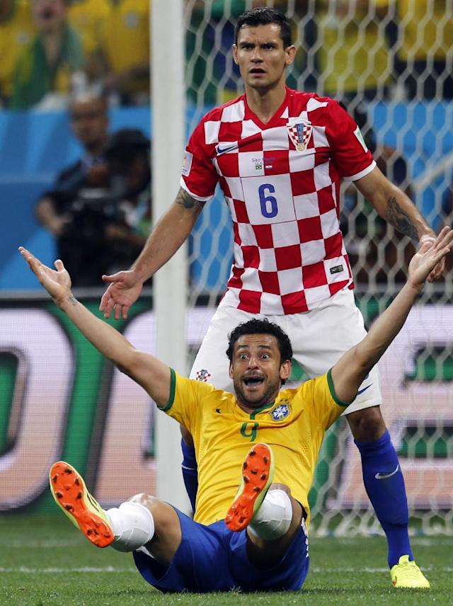 In this Thursday, June 12, 2014 photo, Brazil's Fred raises his arms after a penalty was called against Croatia's Dejan Lovren, top, by referee Yuichi Nishimura, from Japan, during the group A World Cup soccer match between Brazil and Croatia in the opening game of the tournament at the Itaquerao Stadium in Sao Paulo, Brazil. Brazil was issued a penalty kick following the play leading to a goal by Neymar helping Brazil to a 3-1 victory. (AP Photo/Frank Augstein)