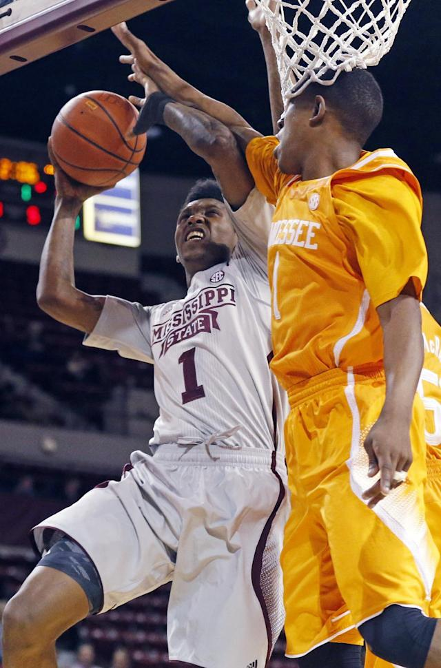 Mississippi State guard Fred Thomas (1) is blocked by Tennessee guard Antonio Barton (1) at his layup attempt in the first half of an NCAA college basketball game in Starkville, Miss., Wednesday, Feb. 26, 2014. (AP Photo/Rogelio V. Solis)