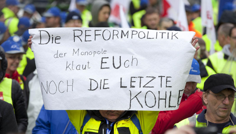Airport ground workers and baggage handlers demonstrate in front of EU headquarters in Brussels, Monday, Nov. 5, 2102. Workers are protesting against a proposal for more competition in the market which they feel will have a negative effect on their working conditions. Sign reads 'The reform policies of the monopolies means that they steal the last of your money'. (AP Photo/Virginia Mayo)