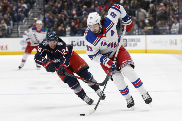New York Rangers' Mika Zibanejad, right, of Sweden, carries the puck across the blue line as Columbus Blue Jackets' Nathan Gerbe defends during the first period of an NHL hockey game Friday, Feb. 14, 2020, in Columbus, Ohio. (AP Photo/Jay LaPrete)
