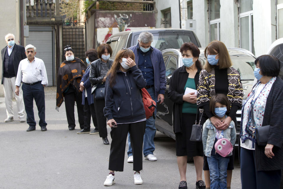 Georgians wearing face masks to help curb the spread of the coronavirus, lineup to vote outside at a polling station during the parliamentary elections in Tbilisi, Georgia, Saturday, Oct. 31, 2020. The hotly contested election between the Georgian Dream party, created by billionaire Bidzina Ivanishvili who made his fortune in Russia and has held a strong majority in parliament for eight years, and an alliance around the country's ex-president who's in self-imposed exile in Ukraine. (AP Photo/Shakh Aivazov)