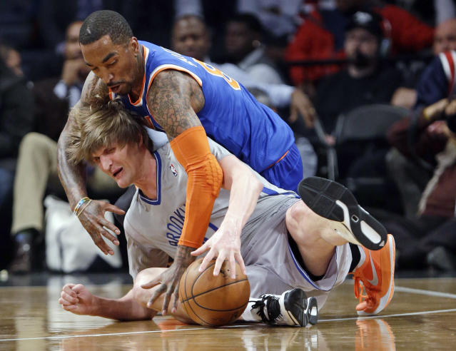 New York Knicks' J.R. Smith, above, and Brooklyn Nets' Andrei Kirilenko, of Russia, scramble for control of the ball during the first half of an NBA basketball game Tuesday, April 15, 2014, in New York. (AP Photo/Frank Franklin II)