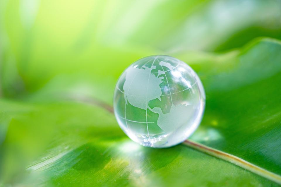 with a glass globe Concept day earth Save the world save environment The world is in the grass of the green bokeh background (Photo: sarayut Thaneerat via Getty Images)