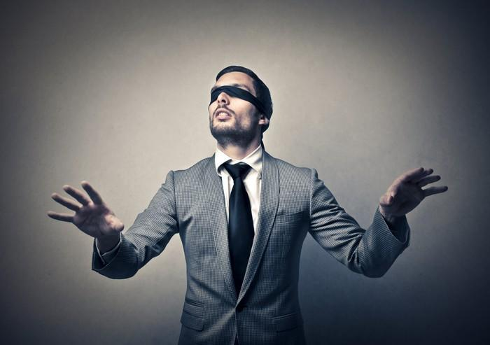 A blindfolded man in a suit reaches out his hands.