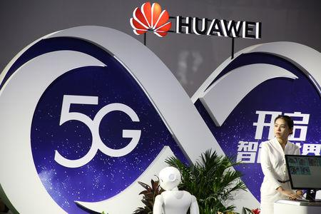 Woman stands at the booth of Huawei featuring 5G technology at the PT Expo in Beijing