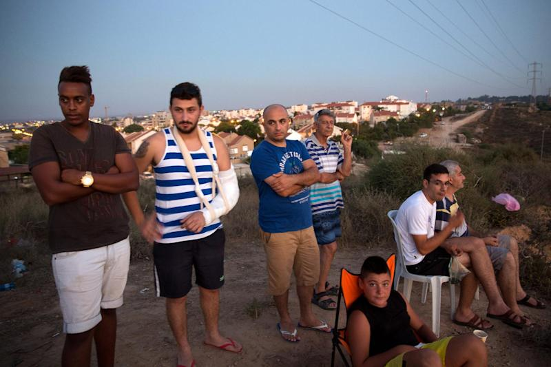 Israelis in the southern city of Sderot stand on a hill overlooking the Gaza Strip to watch the fighting between the Israeli army and Palestinian militants, July 9, 2014 (AFP Photo/Menahem Kahana)