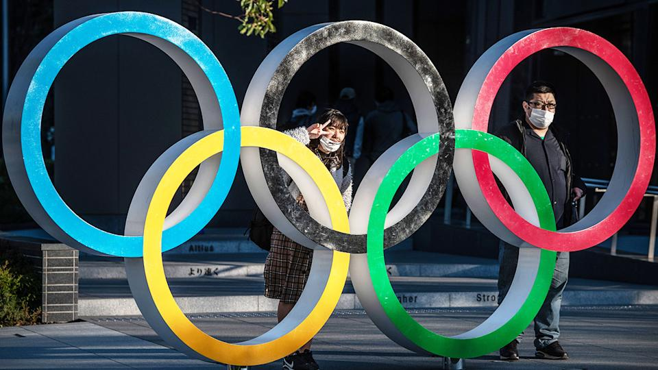 People wearing face masks, pictured here posing for photographs next to the Olympic Rings in Tokyo.
