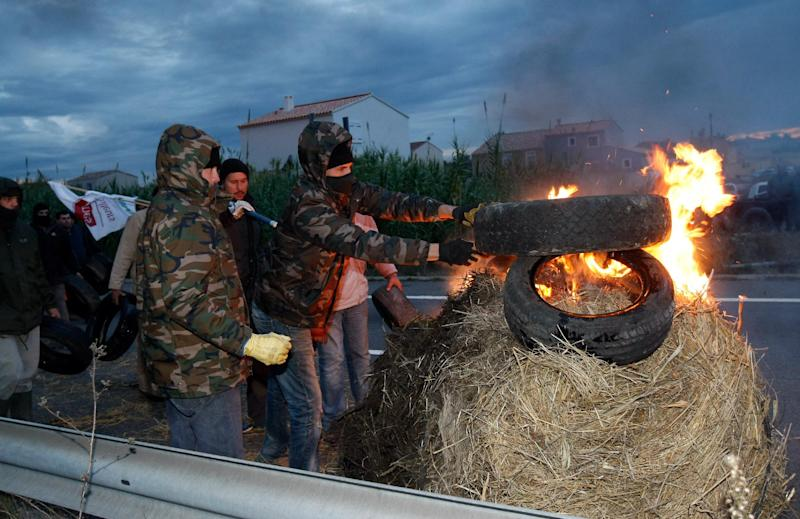 """Farmers burn tires as they block a main road in Arles, southern France,Friday, Nov. 15, 2013. Demonstrators are protesting against the controversial governmental environment """"eco-tax"""". (AP Photo/Claude Paris)"""