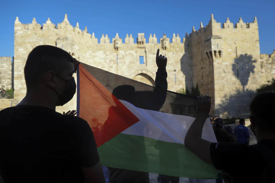 FILE - In this June 19, 2021, file photo, Palestinians demonstrators wave the Palestinian flag during protest in Damascus gate just outside Jerusalem's Old City. A new poll on U.S. attitudes toward a core conflict in the Middle East finds about half of Democrats want the country to do more to support the Palestinians (AP Photo/Mahmoud Illean, File)