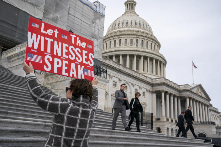 Laura Albinson of Pasadena, Md., displays a message for members of the House as they leave the Capitol in Washington, Friday, Jan. 10, 2020. House Speaker Nancy Pelosi said Friday the House will take steps next week to sent articles of impeachment to the Senate for President Donald Trump's Senate trial. (AP Photo/J. Scott Applewhite)