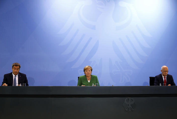 From left, Bavarian State Prime Minister Markus Soeder, German Chancellor Angela Merkel and Mayor of Hamburg Peter Tschentscher attend a news conference following a meeting with leaders of the 16 federal states to discuss the country's response following the spread of the coronavirus, at the Chancellery in Berlin, Thursday, Aug. 27, 2020. In an effort to harmonize different coronavirus measures across the country, Germany will implement a nationwide fine for people not wearing face masks and also ban mass events until the end of the year, Chancellor Angela Merkel said Thursday. (Michele Tantussi/Pool Photo via AP)
