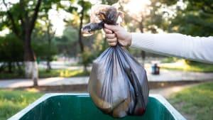 A person throws away garbage.