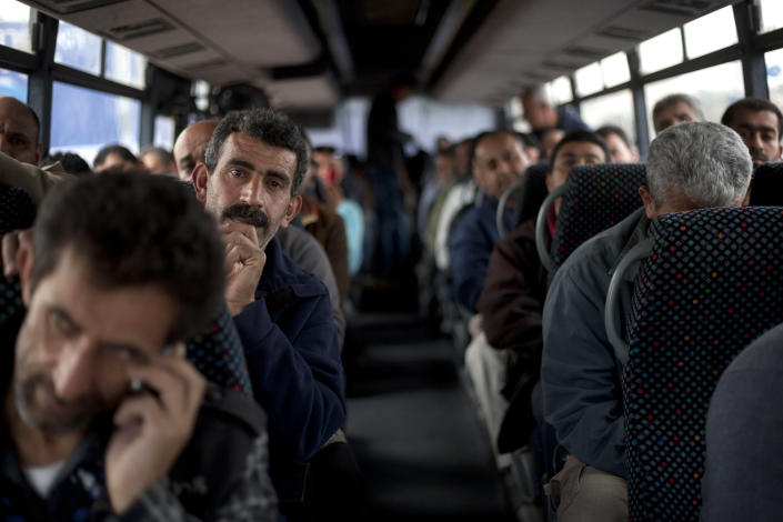"""Palestinians laborers ride a Palestinian-only bus on route to the West Bank from working in Tel Aviv area, Israel, Monday, March 4, 2013. Israel's decision to launch a pair of """"Palestinian-only"""" bus lines in the West Bank condemned by critics as racism and hailed by Israel as a goodwill gesture have shined a light on the messy situation created by 45 years of military occupation and Jewish settlements. (AP Photo/Ariel Schalit)"""