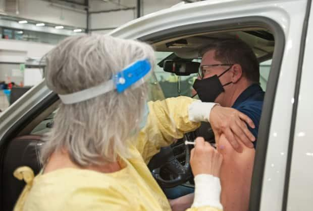 Saskatchewan Premier Scott Moe receives a dose of the Pfizer-BioNTech vaccine at a COVID-19 vaccination drive-thru clinic at Evraz Place in Regina on April 15. As of Friday, Saskatchewan ranked first among Canadian provinces in vaccine administration per capita.