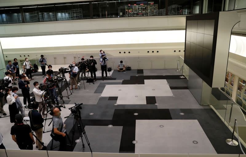 TV camera man wait for the opening of market in front of a large screen showing stock prices at the Tokyo Stock Exchange in Tokyo