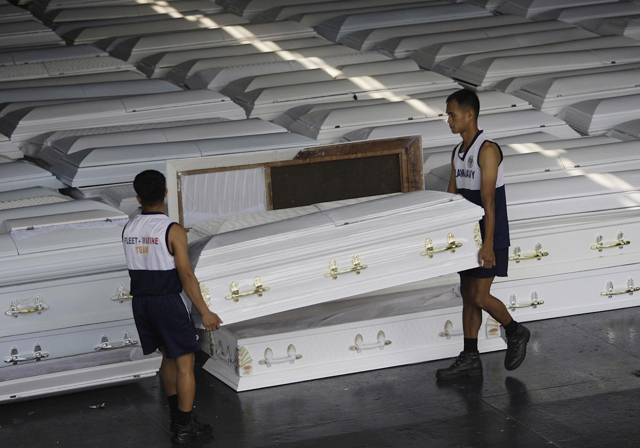 Philippine Navy personnel lift one of coffins that will be shipped with drinking water, clothes and other relief goods to flood-stricken Cagayan De Oro and Iligan cities on board a Philippine Navy ship in Manila, Philippines on Tuesday Dec. 20, 2011. Nearly a thousand people died in massive flash floods when tropical storm Washi hit the country last week in one of the worst disasters to strike the region in decades. (AP Photo/Aaron Favila)