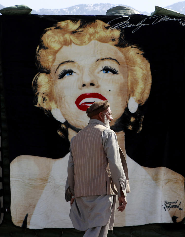 An Afghan vendor waits for customers in front of a blanket with an image of late Hollywood actress Marilyn Monroe at a bazaar in Forward Operating Base Joyce in Kunar province, eastern Afghanistan March 15, 2012. REUTERS/Erik De Castro