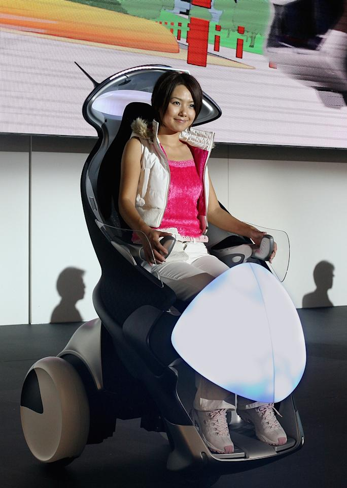 CHIBA, JAPAN - OCTOBER 19: A model tries Toyota Motor Corp's one-seater mobility machine called 'i-swing' during the preview for the 39th Tokyo Motor Show 2005 on October 19, 2005 in Chiba, Japan. The show will be opened to the public from October 22 to November 6. (Photo by Koichi Kamoshida/Getty Images)