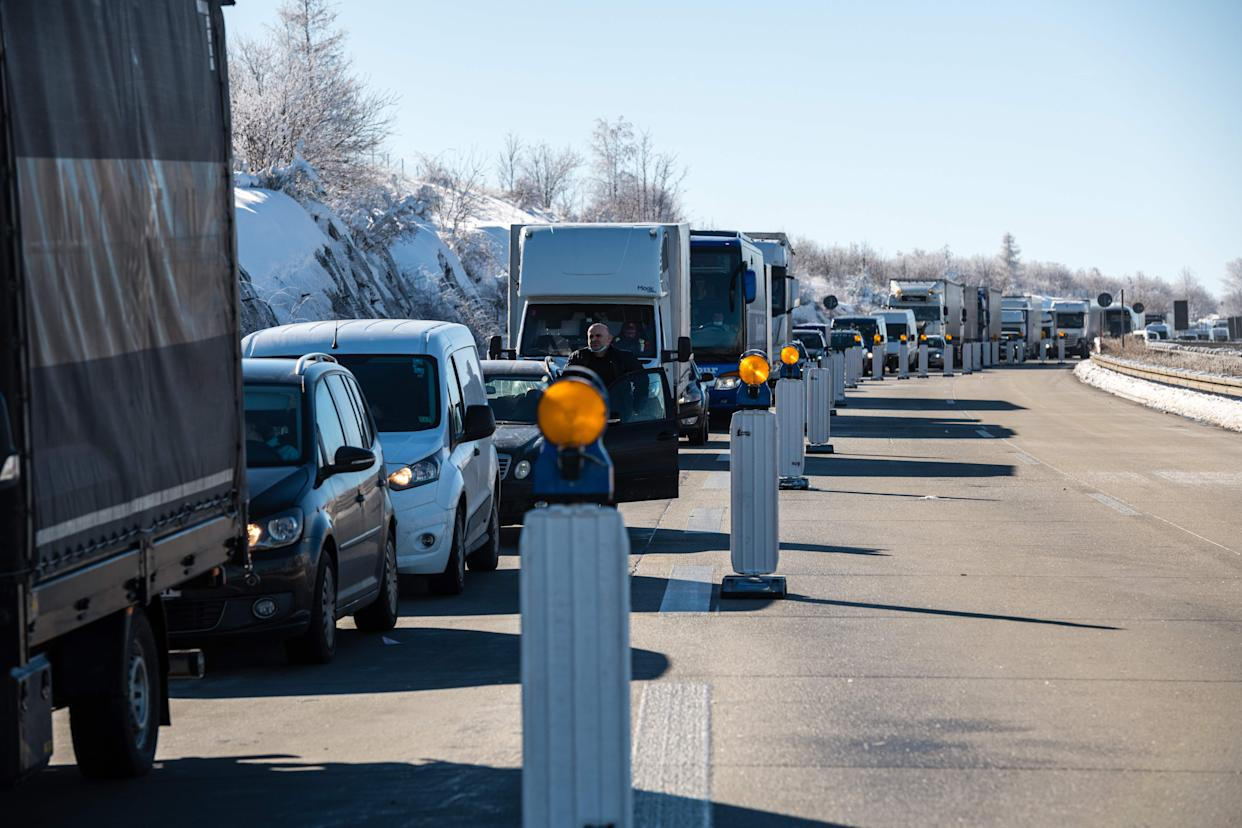 Vehicles wait at a checkpoint of the Federal Police at the German-Czech border near Breitenau, eastern Germany on February 14, 2021. - Germany implemented more measures to keep coronavirus variants at bay, banning travel from Czech border regions and Austria's Tyrol after a troubling surge in contagious mutations. (Photo by JENS SCHLUETER / AFP) (Photo by JENS SCHLUETER/AFP via Getty Images)