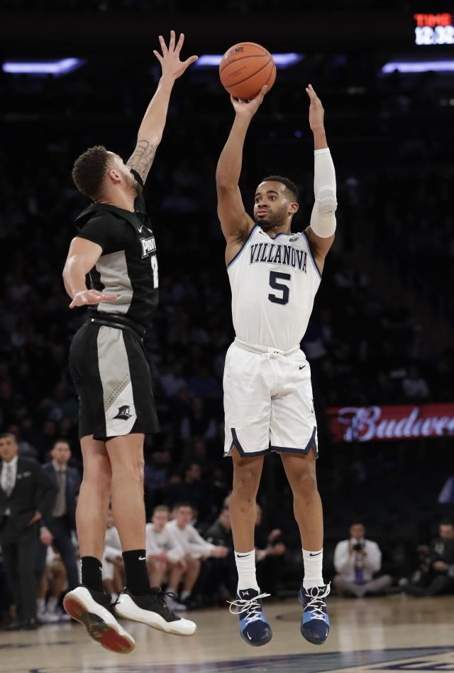 Villanova's Phil Booth, right, shoots 3-point basket over Providence's Drew Edwards during the first half of an NCAA college basketball game in the Big East Conference tournament, Thursday, March 14, 2019, in New York. (AP Photo/Frank Franklin II)