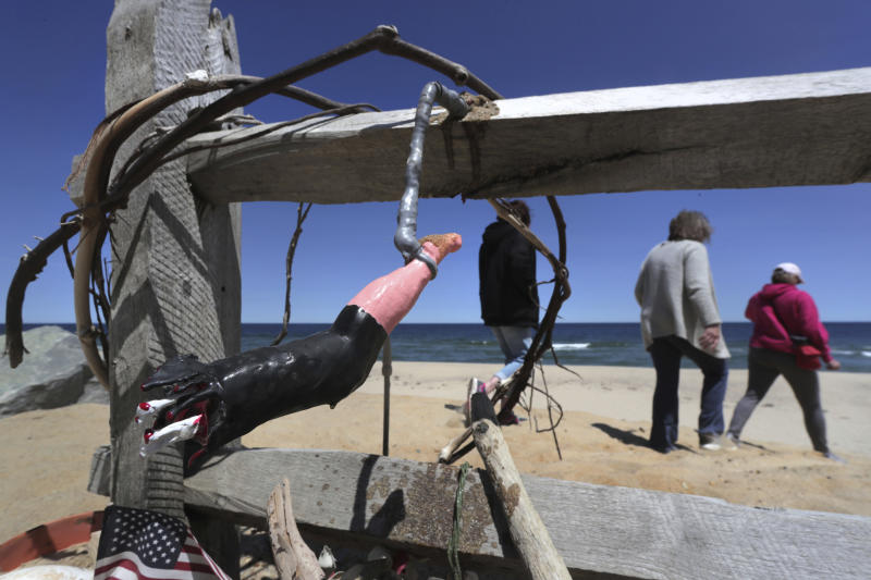 FILE - In this May 22, 2019, file photo, three women pass a makeshift memorial at Newcomb Hollow Beach, where a boogie boarder was bitten by a shark in 2018 and later died of his injuries, in Wellfleet, Mass. Researchers on Cape Cod are launching a new study focused on the hunting and feeding habits of the region's great white sharks following two attacks on humans in 2018, including the state's first fatal one in more than 80 years. (AP Photo/Charles Krupa, File)