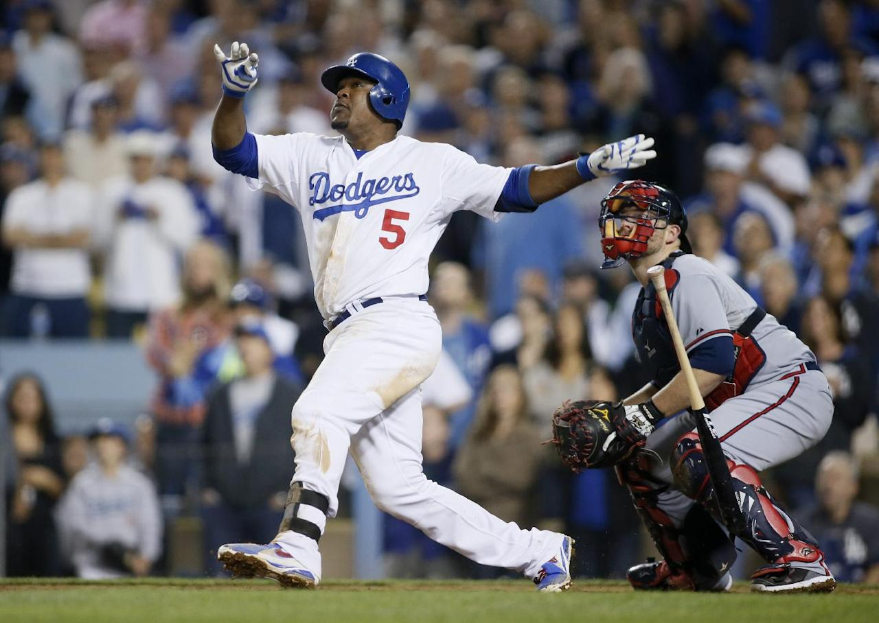 Los Angeles Dodgers third baseman Juan Uribe drops his bat and watches his two-run home run in front of Atlanta Braves catcher Brian McCann in the eighth inning of Game 4 in the National League baseball division series Monday, Oct. 7, 2013, in Los Angeles. (AP Photo/Danny Moloshok)