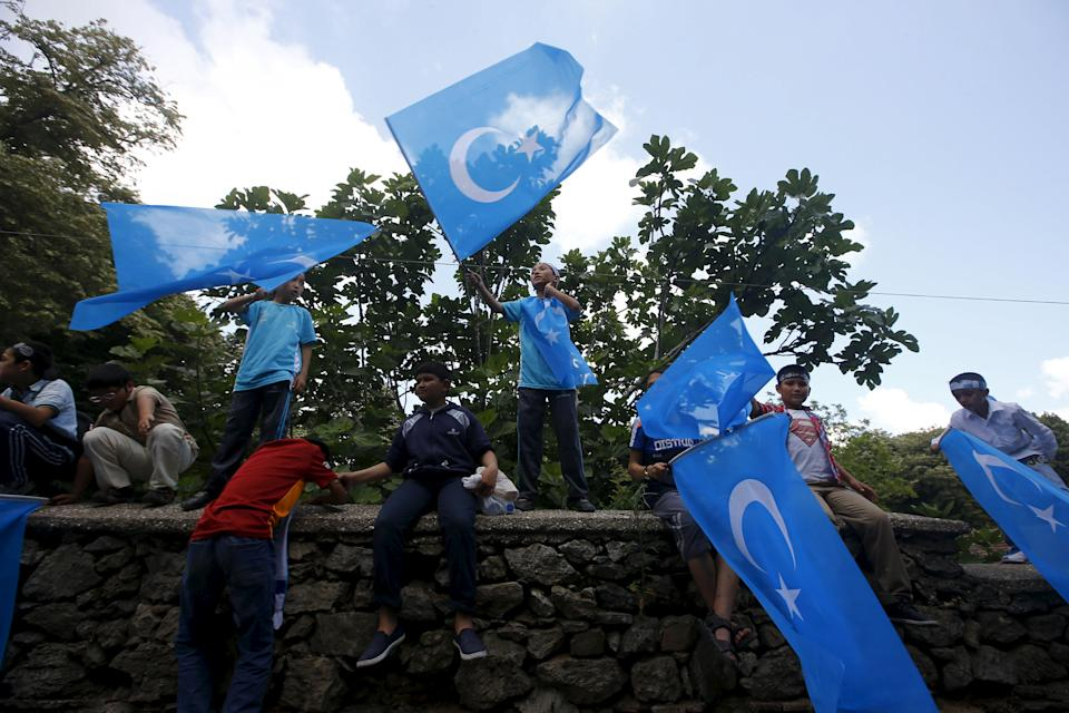 Boys wave East Turkestan flags during a protest against China near the Chinese Consulate in Istanbul, Turkey, July 5, 2015.