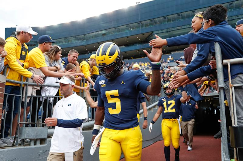 Michigan quarterback Joe Milton high-fives fans as he runs down the tunnel before the Middle Tennessee State game at Michigan Stadium, Saturday, August 31, 2019.