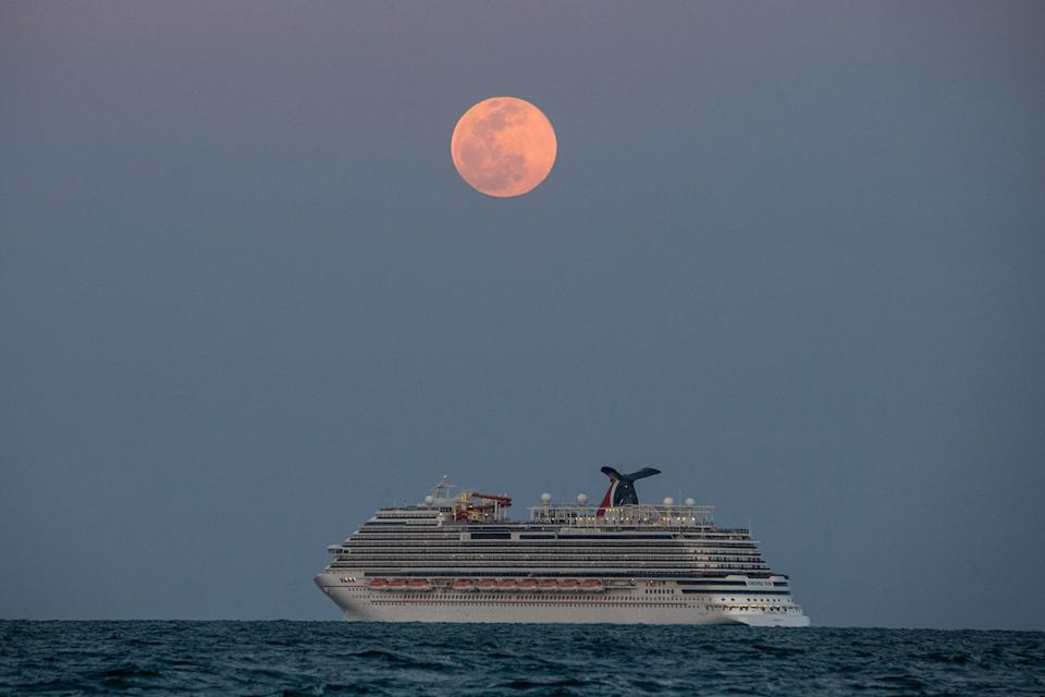 The Carnival Vista cruise ship is seen sailing during a full Pink Super moon in Miami Beach, on April 26, 2021.