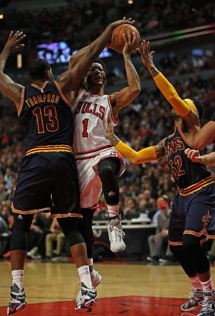 Chicago Bulls' Derrick Rose (C) is fouled as he tries to drive between Cleveland Cavaliers' Tristan Thompson (L) and Mo Williams during the season opening game at United Center on October 27, 2015 (AFP Photo/Jonathan Daniel)