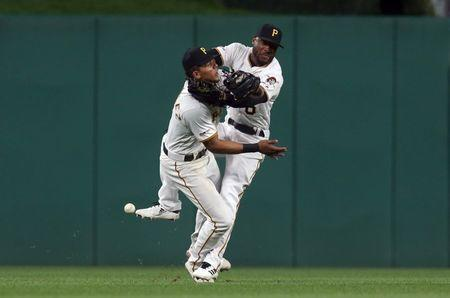 Apr 19, 2019; Pittsburgh, PA, USA; Pittsburgh Pirates shortstop Erik Gonzalez (left) and center fielder Starling Marte (right) collide while chasing a fl yball against the San Francisco Giants during the eighth inning at PNC Park. Both players would leave the game. Mandatory Credit: Charles LeClaire-USA TODAY Sports