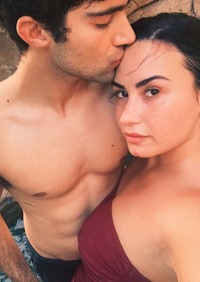 Max Ehrich and Demi Lovato wearing a burgundy swimsuit