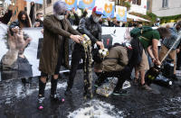 People spill beer on the ground during a protest against the government restriction measures to curb the spread of COVID-19, in Rome, Saturday, Oct. 24, 2020. Italian Premier Giuseppe Conte, who imposed severe-stay-at-home limits on citizens early on, then gradually eased travel and other restrictions, has been leaving it up to regional governors in this current surge of infections to order restrictions such as overnight curfews, including in places like Rome, Milan and Naples. (Mauro Scrobogna/LaPresse via AP)