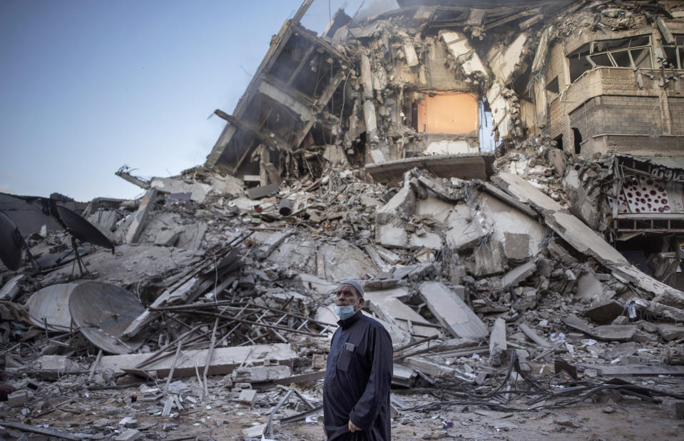 A Palestinian man looks at the destruction of a building hit by Israeli airstrikes in Gaza City, Thursday, May 13, 2021. Gaza braced for more Israeli airstrikes and communal violence raged across Israel after weeks of protests and violence in Jerusalem. (AP Photo/Khalil Hamra)